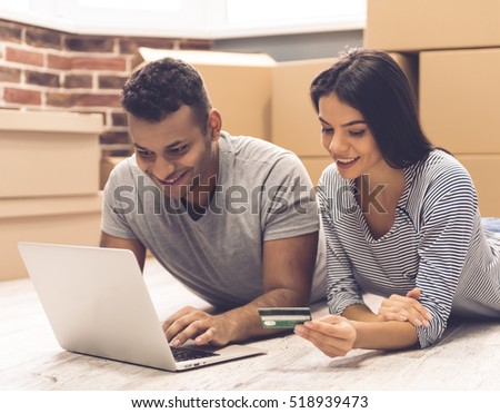 Beautiful couple is using a laptop and smiling while lying on the floor near the moving boxes. Girl is holding a credit card