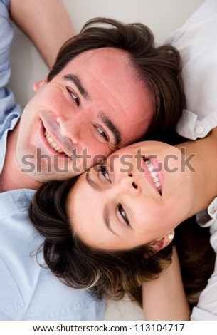 Beautiful couple lying on the floor with heads together