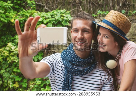 Beautiful couple smiling in your home garden./ Young couple taking selfie with smart phone camera in outdoors.