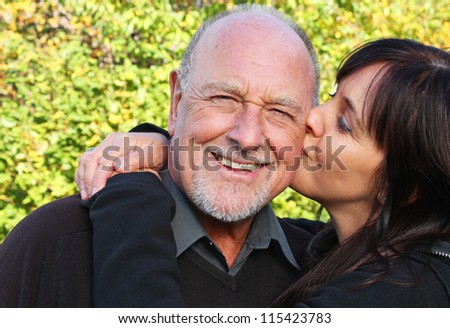 Beautiful daughter kissing her senior father