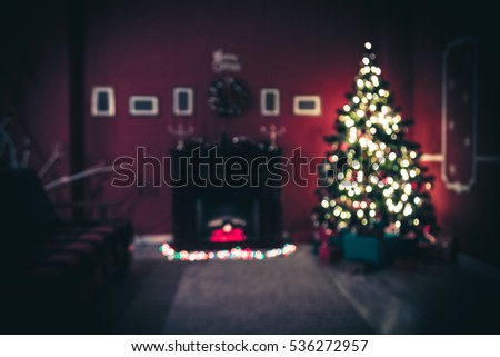 Beautiful Defocused background new year room with decorated Christmas tree, gifts and fireplace with the glowing lights at night