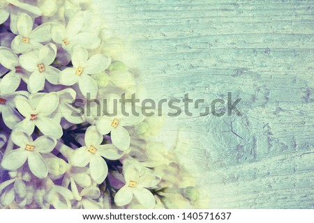 Beautiful delicate lilac on a wooden texture. Vintage style.