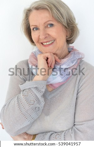 Beautiful elderly lady with a vivacious smile standing with her arms folded grinning happily at the camera in a loose trendy pullover
