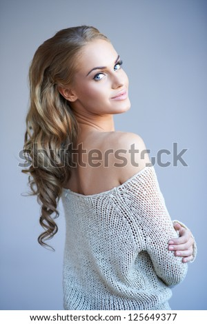 Beautiful elegant woman with long curly blonde hair wearing a stylish off the shoulder top looking back over her shoulder with a smile