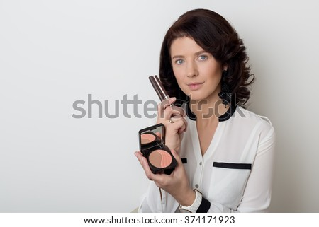 beautiful elegant woman with make-up demonstrates the decorative cosmetic products in jars for applying makeup on a white background in studio