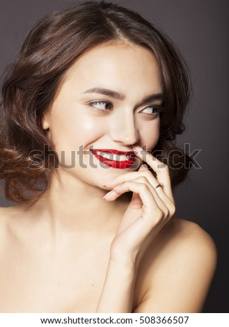 Beautiful elegant young model with red lips.Woman Face on dark b