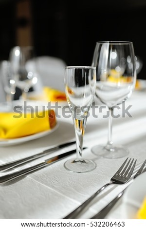 beautiful empty wine glasses and yellow napkin on a decorated table close-up.