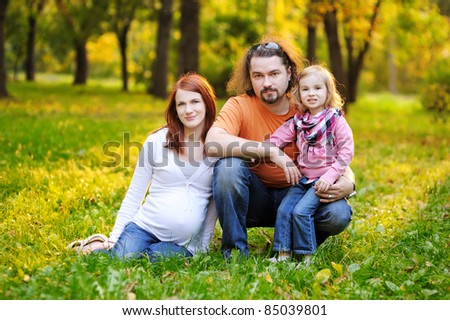 Beautiful expecting family in autumn park at sunset