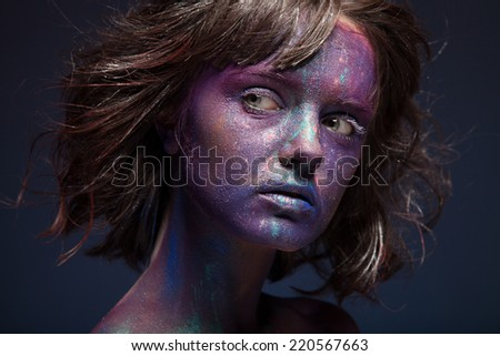 Beautiful face of a woman covered in glitter Close up of a woman's face covered in blue and purple glitter