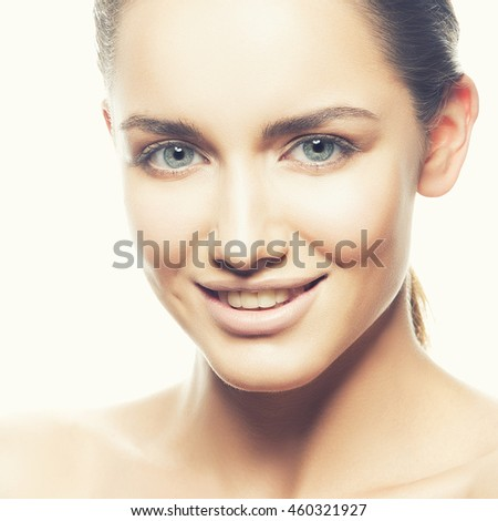 Beautiful face of smiling young caucasian brunette woman with natural lips, make-up, perfect skin and blue eyes isolated on white. Studio portrait. Toned