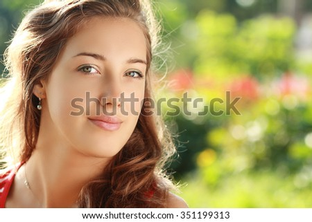 Beautiful face of the young sexy woman posing near the green tree on nature