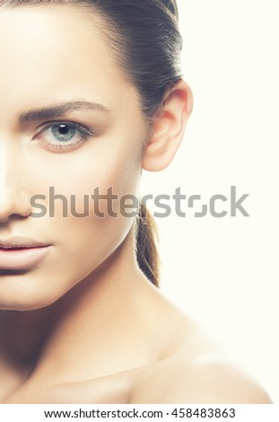 Beautiful face of young caucasian brunette woman with natural lips, make-up, perfect skin and blue eyes isolated on white. Studio portrait. Toned