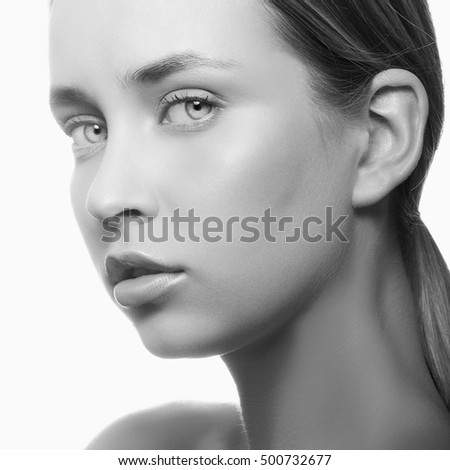 Beautiful face of young caucasian girl with natural make-up, perfect skin and green eyes over white background. Studio portrait. Black and white