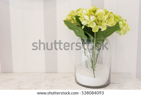 beautiful fake flowers in a glass jar