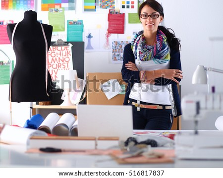 Beautiful fashion woman designer standing in studio