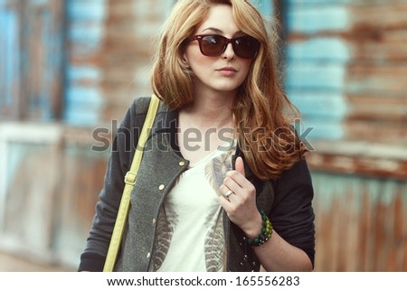 Beautiful fashionable woman in sunglasses walking in the street