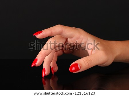 Beautiful female hands with red nails isolated on black