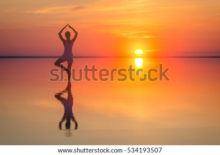 Beautiful female model open arms under the sunrise at seaside. Calm water of salt lake Elton reflects silhouette of woman. Sun goes under horizon. Girl stands alone in water. Astrakhan region.