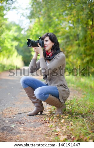 beautiful female photographer takes photo outdoor
