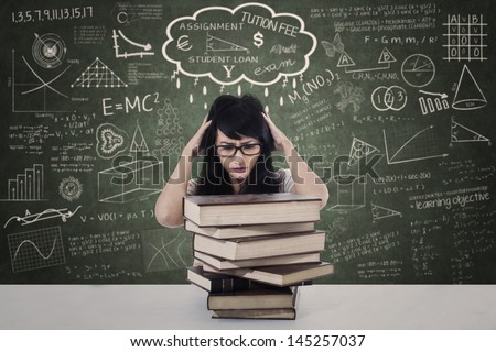 Beautiful female stressing out due to exam with pile of books in class