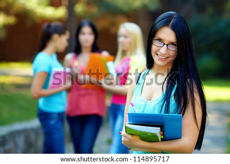 beautiful female student outdoors with a group of people on the background
