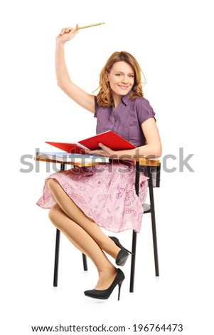 Beautiful female student with raised hand seated in a school desk isolated on white background