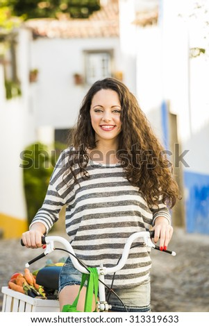 Beautiful female tourist living like a local, with her bicycle after buying some fresh vegetables