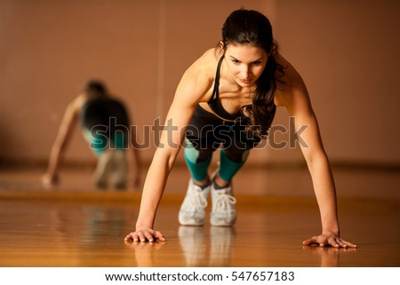 beautiful fit woman works out in a fitness gym making push ups for body strength