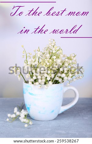 Beautiful flowers in cup on table on light background, Mother's Day concept