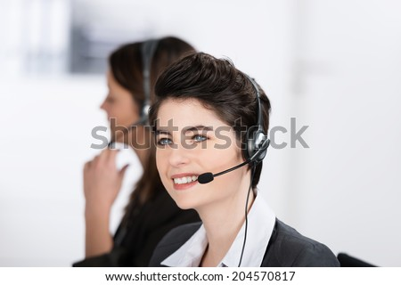 Beautiful friendly call center operator wearing a headset sitting looking up into the air as she listens to the conversation with a client with a smile
