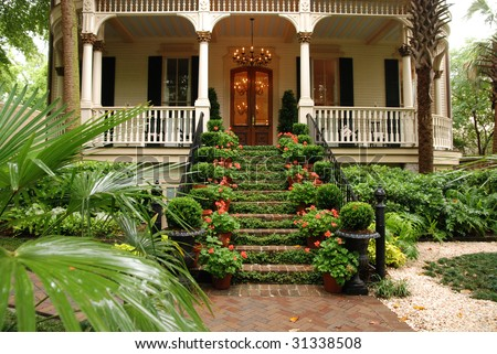 Beautiful front stairs and yard of historic colonial home with flowers and ivy