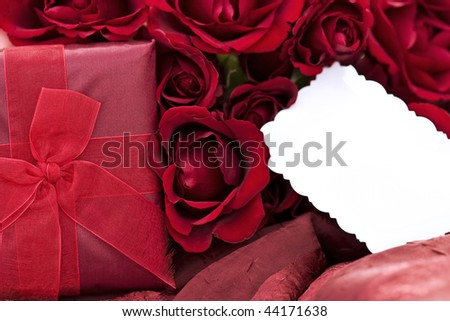 dozen red roses and blank card lying on a two toned red background ...