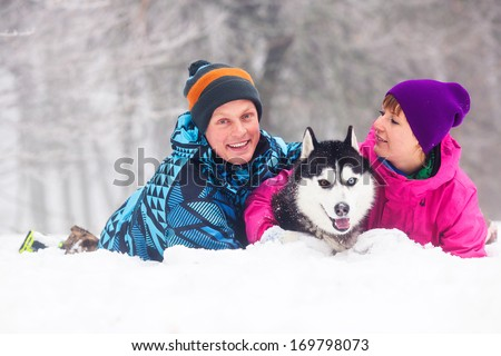 Beautiful girl and boy walking with husky dog in winter forest