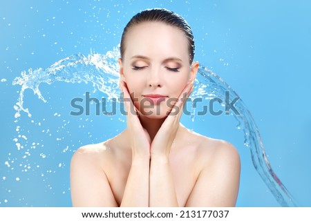 Beautiful girl and stream of water on blue background