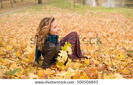 Beautiful girl blonde with wavy hair wearing a blue scarf lying on yellow leaves
