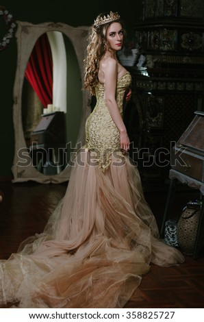 beautiful girl in a long yellow dress and a crown on his head is standing next to a large vintage mirror