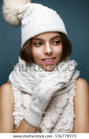 Beautiful girl in a white knitted hat with fur pompom. Model with gentle nude make-up. Cozy winter picture. Beauty face.