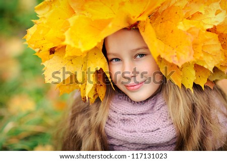 Beautiful girl in autumn leaves. Yellow maple wreath on his head. Happy baby.