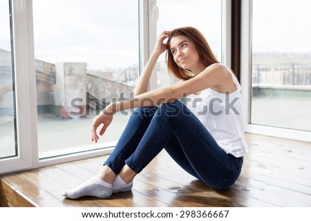 beautiful girl in blue jeans sitting on the floor and smiling