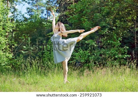 Beautiful girl in dress in pose of swallows in clearing in woods
