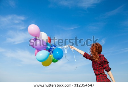 Beautiful girl in plaid dress with multicolored balloons on blue sky background