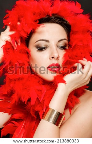 Beautiful girl in red boa with bright makeup