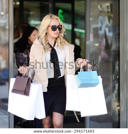 beautiful girl in sunglasses out of the store with shopping