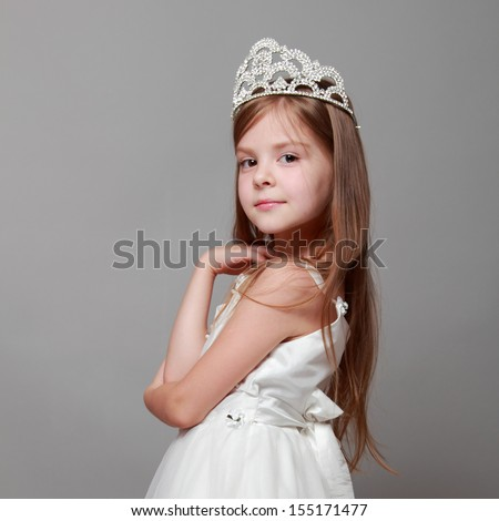 Beautiful girl is putting on a diamond diadem on Beauty and Fashion/Young princess smiling and posing for the camera