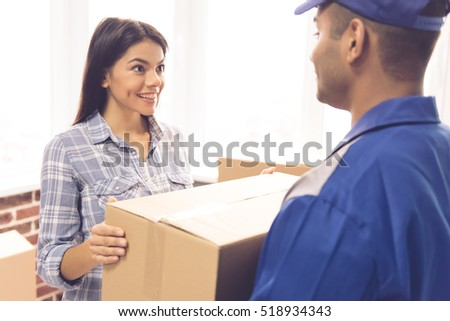 Beautiful girl is smiling while getting a delivery. Handsome worker is holding a box