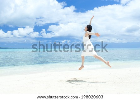 beautiful girl jumping on the tropical island beach