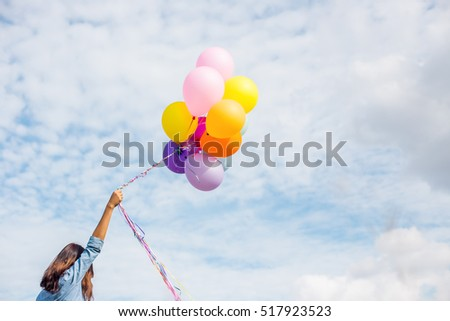 Beautiful Girl jumping with balloons on the beach