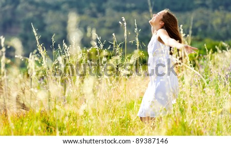 beautiful girl laughs and dances outdoors in a meadow during sunset