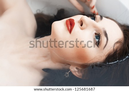 Beautiful girl lying in the bathroom, red lips closeup