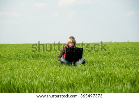 Beautiful girl outdoors sits with laptop on fresh green herb